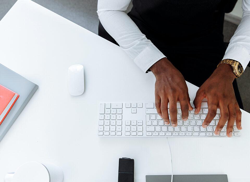 homem digitando em uma teclado branco