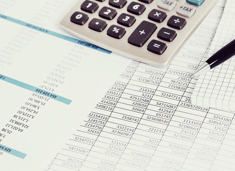 mesa com folha, calculadora e caneta
