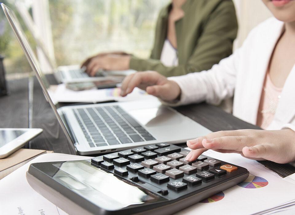 pessoas em uma mesa mexendo na calculadora e no notebook