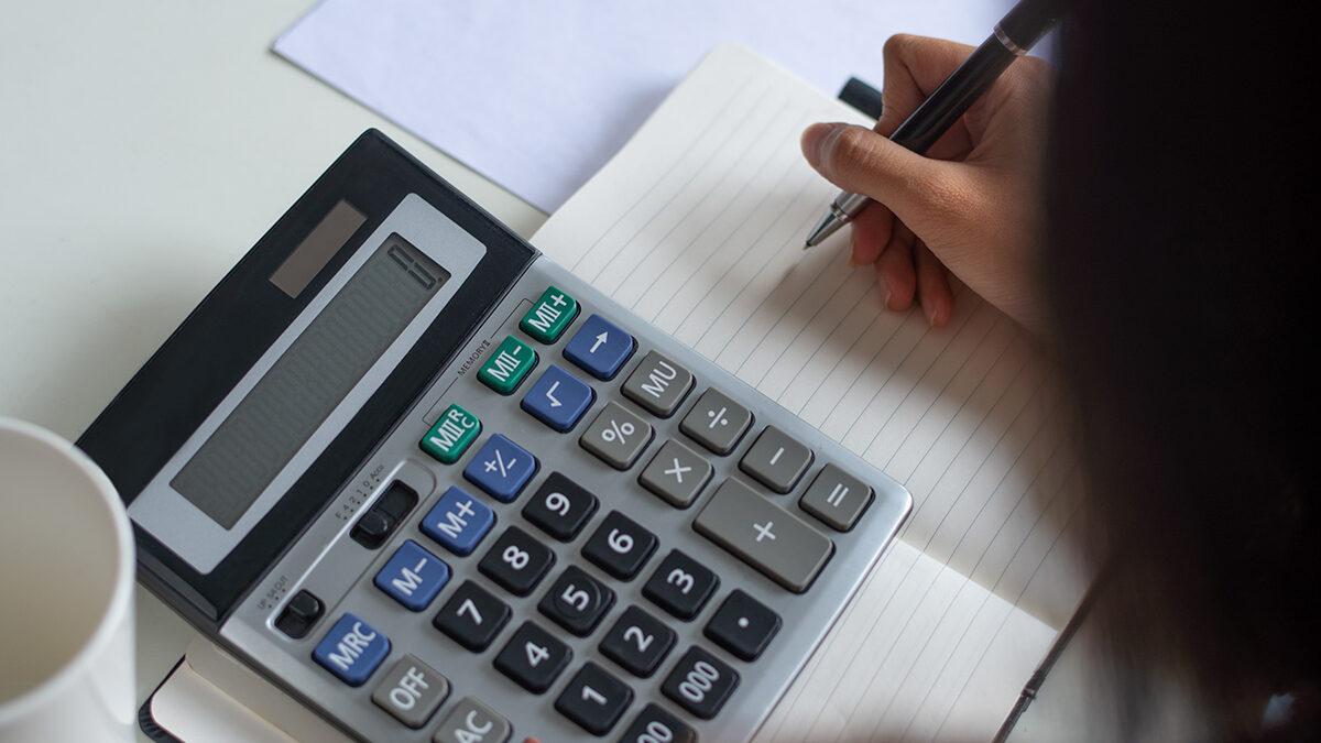 pessoa escrevendo olhando calculadora