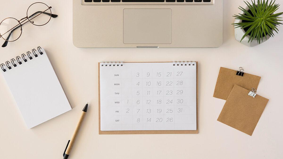 mesa com notebook, bloco de notas e calendário em cima dela